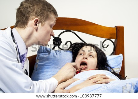 doctor treats the patient's throat at his home - stock photo