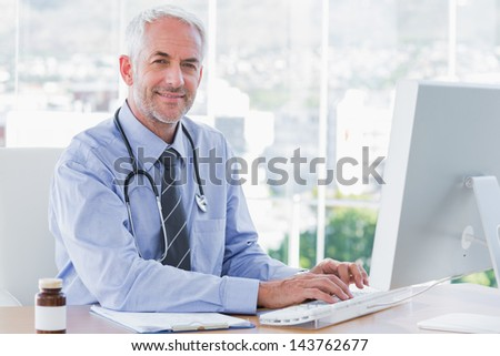 Doctor typing and using his computer in the office - stock photo