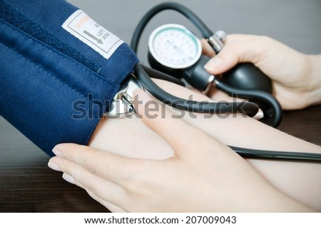 Doctor uses a sphygmomanometer  - stock photo