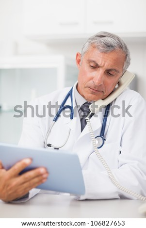 Doctor using a tablet computer while calling in medical office - stock photo