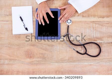 Doctor using digital tablet on desk - stock photo