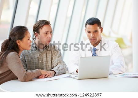Doctor Using Laptop Discussing Treatment With Patients - stock photo