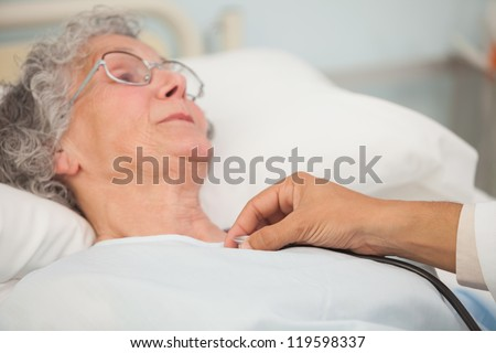 Doctor using stethoscope on elderly female patient in hospital bed - stock photo