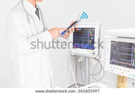 Doctor using tablet computer with medical instrument - stock photo