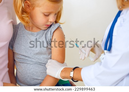 Doctor vaccinating small redhead girl. - stock photo