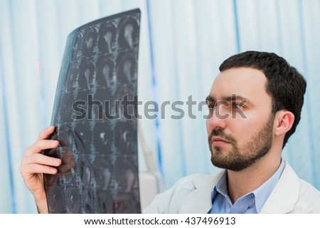Doctor viewing MRI scans at his office - stock photo