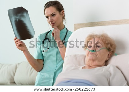 Doctor watching x-ray photography of elder woman - stock photo