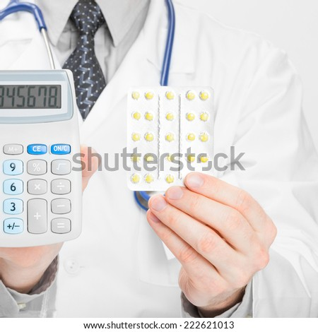 Doctor with calculator and pills in hands - 1 to 1 ratio - stock photo