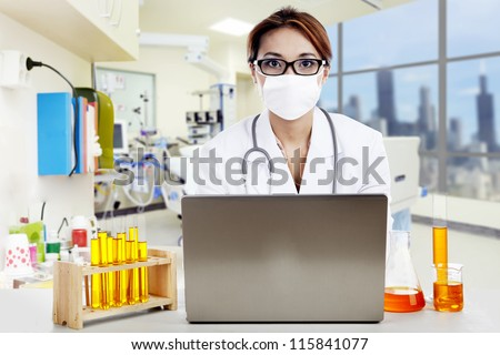 Doctor with chemicals working on laptop in a clinic - stock photo