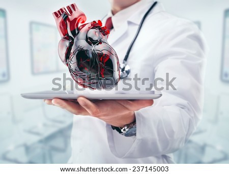 Doctor with heart in hands in a hospital - stock photo