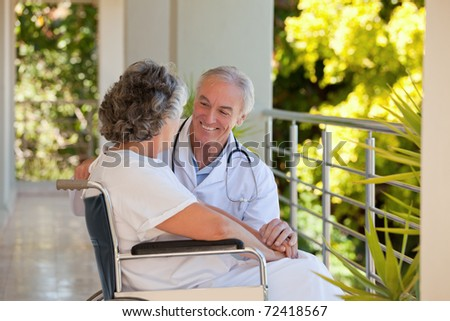 Doctor with his patient in her wheelchair - stock photo