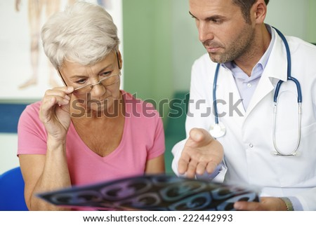 Doctor with his senior patient analyzing medical test  - stock photo