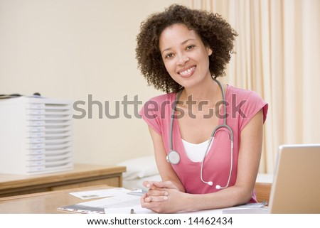 Doctor with laptop in doctor's office smiling - stock photo