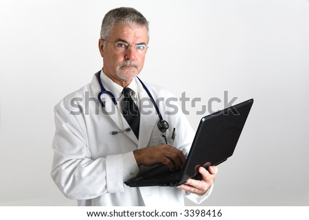 Doctor with laptop looking at the camera with a laptop in his hands - stock photo