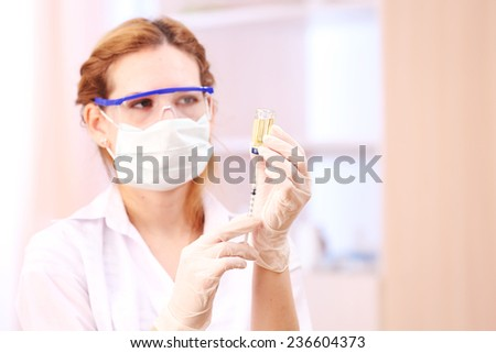 Doctor with medical syringe in hands, getting ready for injection - stock photo