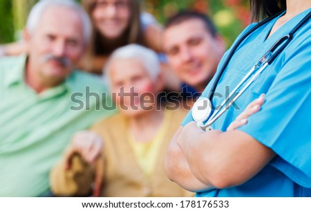 Doctor with stethoscope and happy family in the background medical care concept. - stock photo