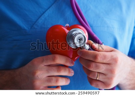 Doctor with stethoscope examining red heart, isolated on white background - stock photo