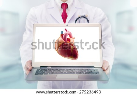 Doctor with stethoscope in a hospital. Heart on the laptop monitor. High resolution.  - stock photo