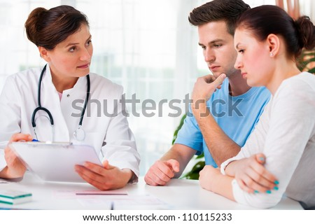 doctor woman offering medical advices to a young couple in office - stock photo
