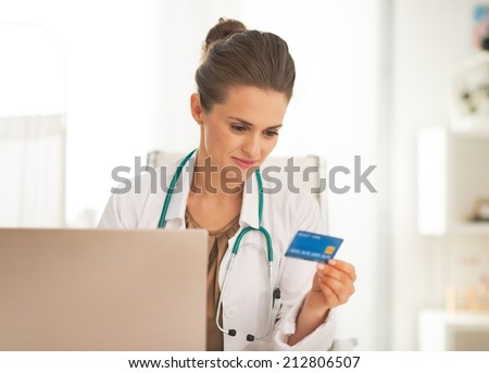 Doctor woman with credit card making online shopping - stock photo