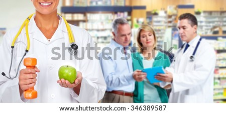 Doctor woman with dumbbell and apple over health care background. - stock photo