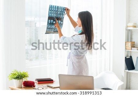 Doctor woman with white labcoat looking at x-ray radiographic results ct scan mri in  hospital clinic - stock photo