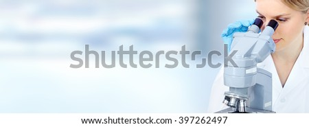 Doctor woman  working with a microscope. - stock photo