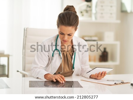 Doctor woman working with fluorography in office - stock photo