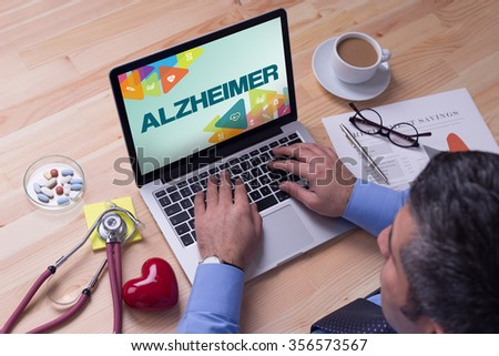 Doctor working on a laptop and ALZHEIMER on his screen - stock photo