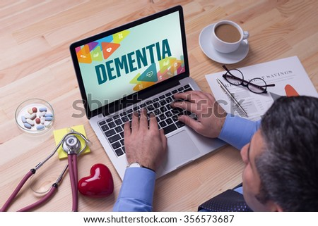 Doctor working on a laptop and DEMENTIA on his screen - stock photo