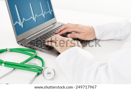 doctor working on laptop with heart rhythm ekg on screen close up - stock photo