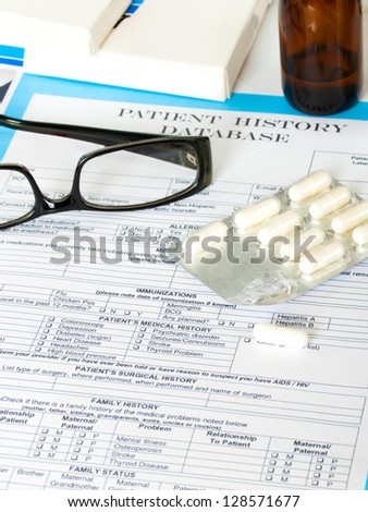 Doctor workplace. Pills, tablets, glasses on patient history database - stock photo