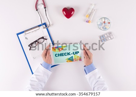 Doctor workplace with CHECK-UP on tablet - stock photo