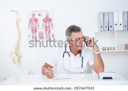 Doctor writing on clipboard and phoning in medical office - stock photo