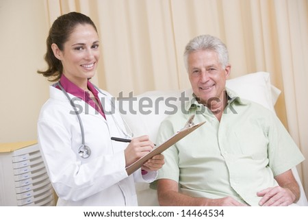 Doctor writing on clipboard while giving checkup to man in exam room smiling - stock photo
