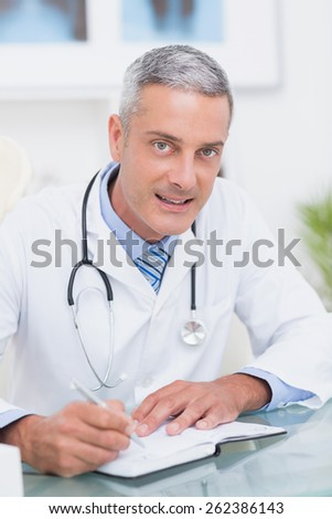 Doctor writing on diary at his desk in medical office - stock photo