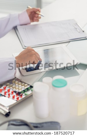 Doctor writing out a prescription using a digital tablet - stock photo