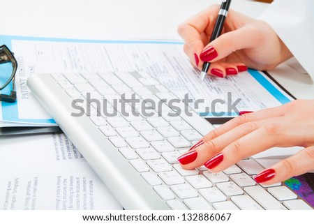 Doctor writing prescription and work with keyboard. Selective focus - stock photo