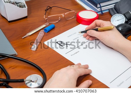 Doctor writing prescription with pills and stethoscope - stock photo