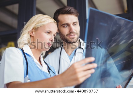 Doctors analysing X-ray while standing at hostiptal - stock photo
