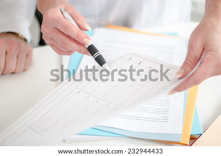 Doctors analyzing an electrocardiogram at office - stock photo