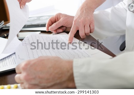 Doctors analyzing an electrocardiogram in medical office - stock photo