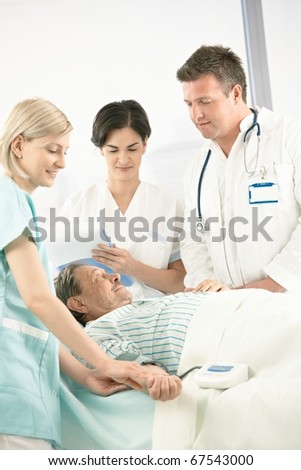Doctors and nurse examining old patient in hospital, nurse measuring blood pressure.? - stock photo