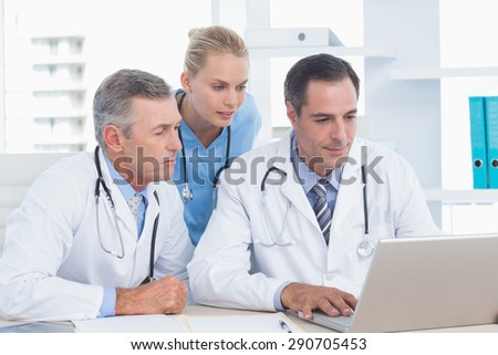 Doctors and nurse working with computer in medical office - stock photo
