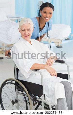 doctors and patient in wheelchair at the hospital - stock photo
