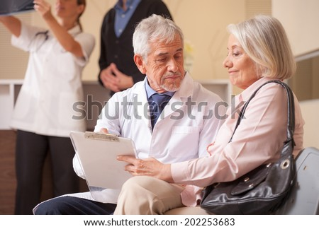 Doctors and patients in hospital waiting room. Senior male doctor explaining medical exams to woman patient. - stock photo