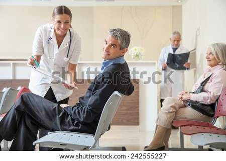 Doctors and patients speaking in the hospital waiting room. - stock photo
