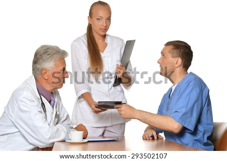 Doctors at the table exemining xray   on white background - stock photo