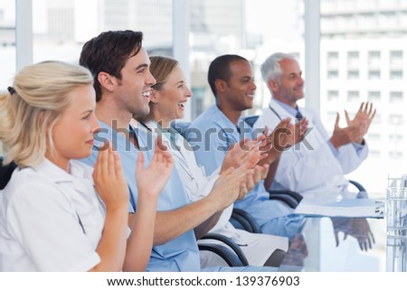 Doctors clapping their hands during a conference - stock photo