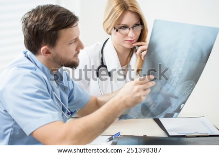 Doctors consulting x-ray of the pelvis - stock photo